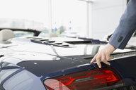 Man looking at convertible in car dealership showroom - HEROF07856