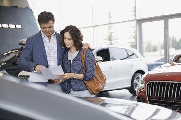Couple looking at brochure in car dealership showroom - HEROF07889
