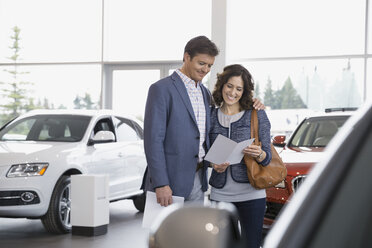 Couple looking at brochure in car dealership showroom - HEROF07892