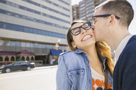 Enthusiastic couple kissing on sunny urban street - HEROF07898