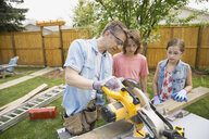 Father teaching children to use table saw - HEROF07919