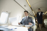 Flight attendant approaching businessman on corporate jet - HEROF07970