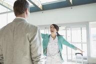 Enthusiastic woman greeting man in airport - HEROF08021