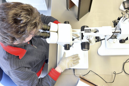 Woman using a microscope for the quality control in the manufacturing of ceramic circuit boards for the electronics industry - LYF00902