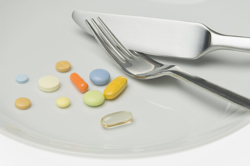Pills on a plate with cutlery - CRF02810