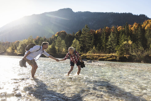 Austria, Alps, couple on a hiking trip wading in a brook - UUF16536