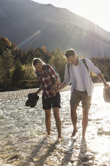 Austria, Alps, couple on a hiking trip wading in a brook - UUF16539