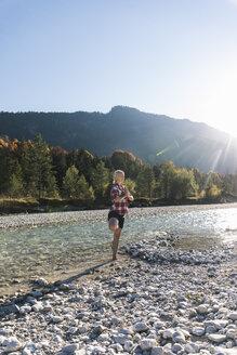 Austria, Alps, woman practicing yoga in a mountain brook - UUF16548