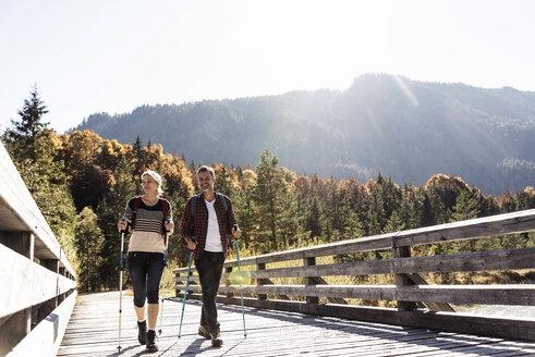 Austria, Alps, couple on a hiking trip crossing a bridge - UUF16551