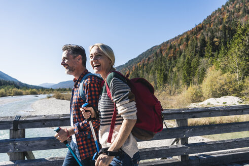 Austria, Alps, happy couple on a hiking trip crossing a bridge - UUF16554