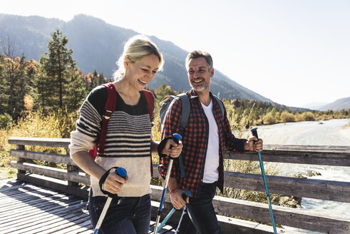 Austria, Alps, happy couple on a hiking trip crossing a bridge - UUF16557