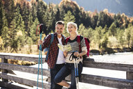 Austria, Alps, happy couple on a hiking trip with map on a bridge - UUF16560
