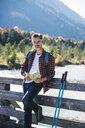 Austria, Alps, man on a hiking trip with map on a bridge - UUF16563