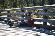 Austria, Alps, woman on a hiking having a break sitting on a bridge - UUF16569