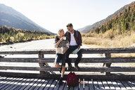 Austria, Alps, couple on a hiking trip having a break on a bridge - UUF16572