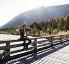 Austria, Alps, man on a hiking trip having a break on a bridge - UUF16575