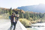 Austria, Alps, couple on a hiking trip with man looking through binoculars - UUF16578