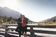 Austria, Alps, happy couple on a hiking trip standing on a bridge - UUF16584