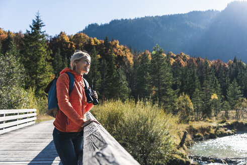 Austria, Alps, woman on a hiking trip standing on a bridge with binoculars - UUF16587