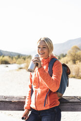 Austria, Alps, happy woman on a hiking trip drinking from bottle - UUF16590