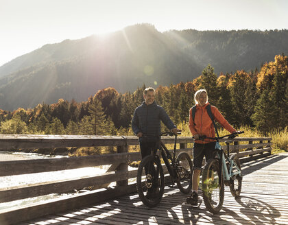 Austria, Alps, couple with mountain bikes crossing a bridge - UUF16593