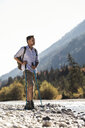 Austria, Alps, man on a hiking trip standing on pebbles at a brook - UUF16602