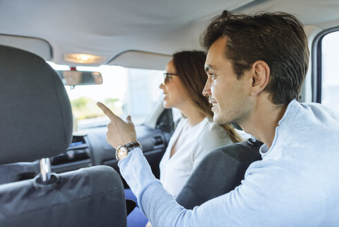 Couple in car with woman on front passenger seat and man pointing his finger from the back seat - KIJF02228