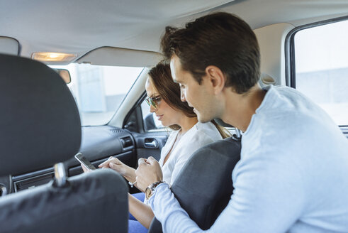 Couple in car with man on back seat and woman with cell phone on front passenger seat - KIJF02231