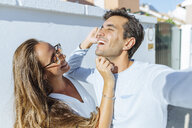 Happy playful couple outdoors on a sunny day - KIJF02246