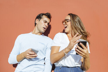 Couple with cell phones outdoors on a sunny day - KIJF02252