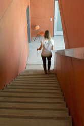 Back view of woman walking down stairs - CRF02819