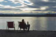 Germany, man sitting at lakeshore of Ammersee with glass of beer watching sunset - CRF02823