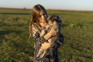 Portrait of content girl with dog on her arms at sunset - ERRF00669