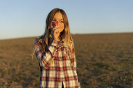 Portrait of smiling blond girl with lollipop at sunset - ERRF00672