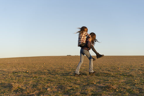 Girl giving her sister a piggyback ride outdoors - ERRF00675