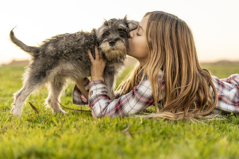 Girl lying on a meadow kissing her dog - ERRF00687