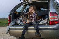 Portrait of girl sitting in opened boot with her dog pouting mouth - ERRF00714