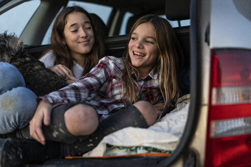 Two sisters in boot of parked car watching sunset - ERRF00717