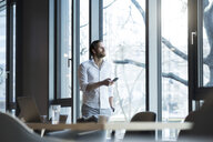 Casual entrepreneur looking out of window in modern office space holding smartphone - SBOF01623