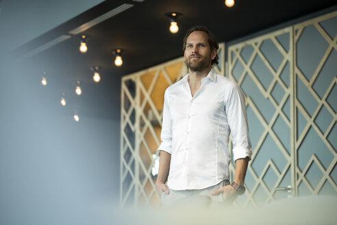 Confident entrepreneur standing in office lounge - SBOF01626