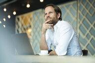 Casual pensative entrepreneur working on laptop in office lounge - SBOF01629