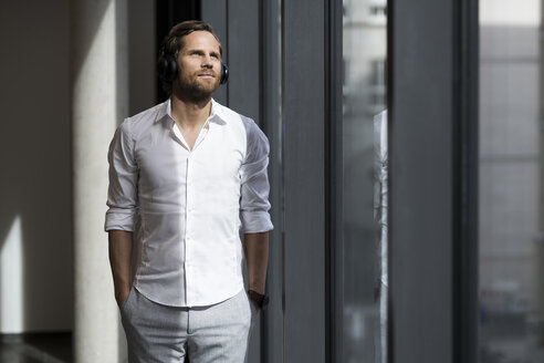 Casual business man with headphones looking out of window in modern office space listening to podcast - SBOF01647