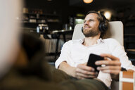 Casual businessman relaxing in lounge area of a coworking space, listening music - SBOF01656
