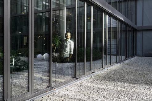 Pensative business man looking outside of large window front in modern office building - SBOF01665