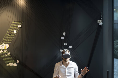 Business man with virtual reality glasses and tablet sitting in modern office - SBOF01668