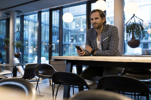 Portrait of confident smart entrepreneur in modern office lounge, using smartphone - SBOF01674