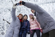 Family with two kids on the ice rink, taking selfies with their smartphone - ZEDF01832