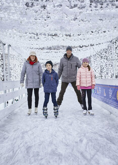 Family with two kids ice skating on the ice rink - ZEDF01835