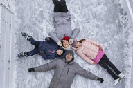 Family with two kids on the ice rink, lying on the ice - ZEDF01844