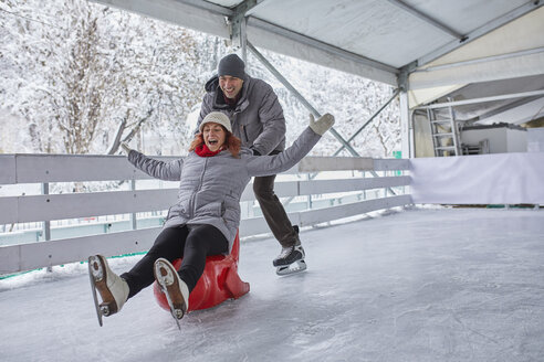 Couple ice skating, using seal sledge to push woman - ZEDF01850